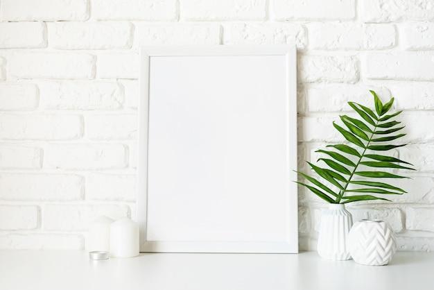 Plakatschablonenmodell mit weißen vasen und blättern auf weißem backsteinmauerhintergrund. speicherplatz kopieren