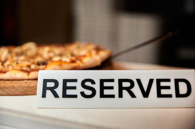 Plakette mit reservierter inschrift neben einer pizza in einem restaurant