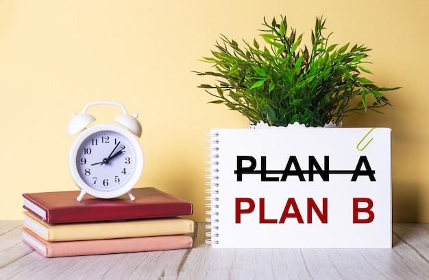 Plan b steht in einem notizbuch neben einer grünen pflanze und einem weißen wecker, der auf bunten tagebüchern steht.