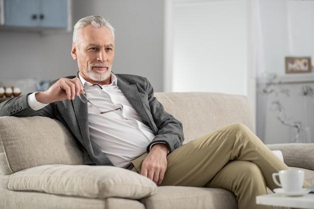 Plan erstellen. hübscher bärtiger mann, der positivität ausdrückt, während brille in der rechten hand hält, auf dem sofa sitzend