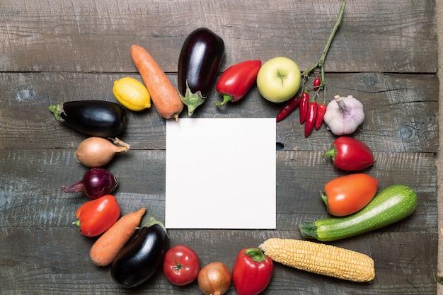 Plan mit verschiedenem gemüse und früchten und weißbuchkarte für text.
