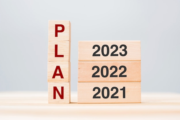 Plan-text mit holzbausteinen 2023, 2022 und 2021 auf tischhintergrund. risikomanagement, resolution, strategie, lösung, ziel, new year new you und happy holiday konzepte