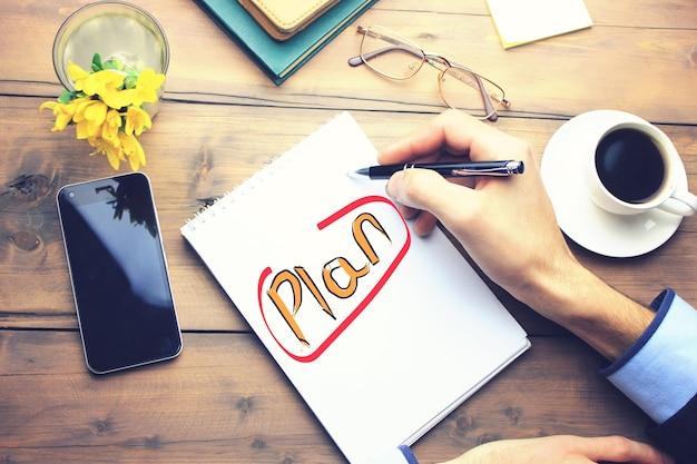 Planen sie auf papier auf einem funktionierenden holztisch