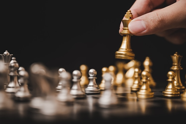Planen sie die führende strategie eines erfolgreichen geschäftswettbewerbsführerkonzepts, das schachbrettspiel der hand des spielers, das goldbauern setzt