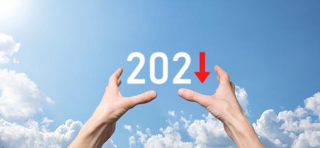 Planen sie ein negatives geschäftswachstum im jahr 2021-konzept. geschäftsmann planen und erhöhen negative indikatoren in seinem geschäft, lehnen geschäftskonzepte ab. hand halten auf himmelshintergrund.