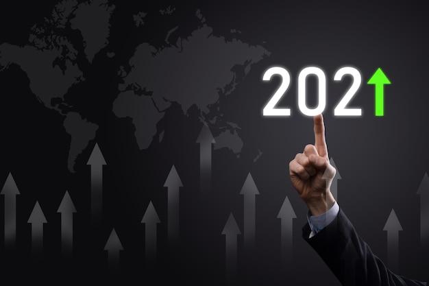 Planen sie ein positives geschäftswachstum im konzept des jahres 2021. geschäftsmann planen und erhöhen positive indikatoren in seinem geschäft, aufwachsen von geschäftskonzepten.