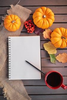 Planen sie eine liste der herbststimmungskomposition auf einem holztisch mit kürbis-eberesche und blättern. öffnen sie notizblock und kaffee in der roten tasse und auf dem grauen holztisch