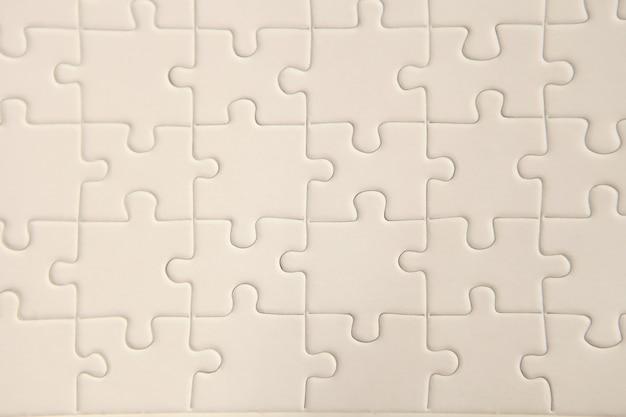 Planen sie eine weiße puzzleoberfläche für strukturierten hintergrund und abstrahierte tapeten. platz für text kopieren