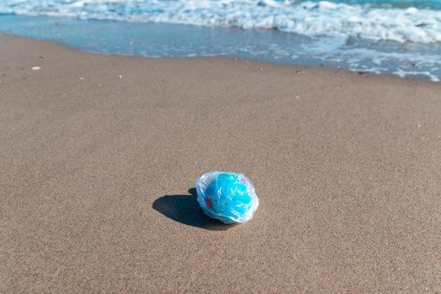 Planetenball in einer plastiktüte auf dem meer. umweltverschmutzung-konzept.