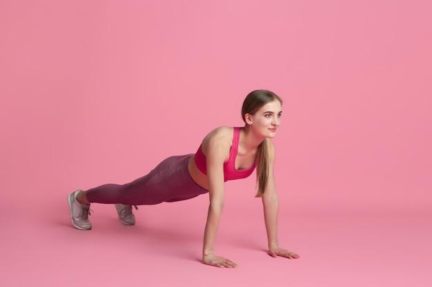 Planke ausbalanciert. schöne junge sportlerin, die im studio übt, einfarbiges rosa porträt.