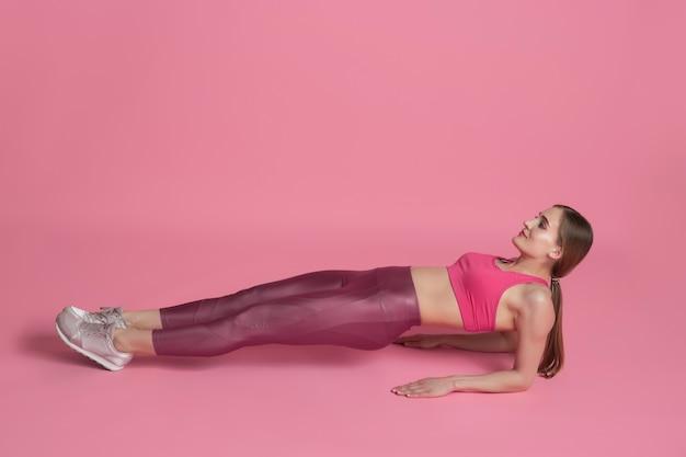 Planke ausbalanciert. schöne junge sportlerin üben, einfarbiges rosa porträt. kaukasisches modelltraining mit sportlicher passform. bodybuilding, gesunder lebensstil, schönheits- und aktionskonzept.