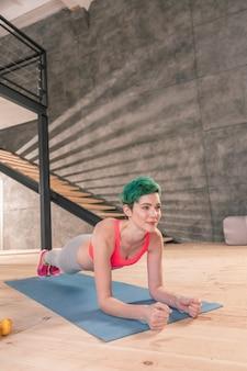 Planke nach yoga. fit junge ansprechende frau mit kurzem haarschnitt macht morgenplanke nach yoga