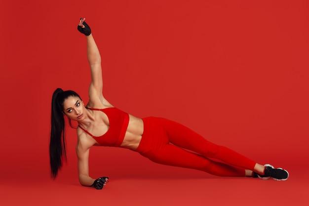 Planke. schöne junge sportlerin, die im studio übt, monochromes rotes porträt.
