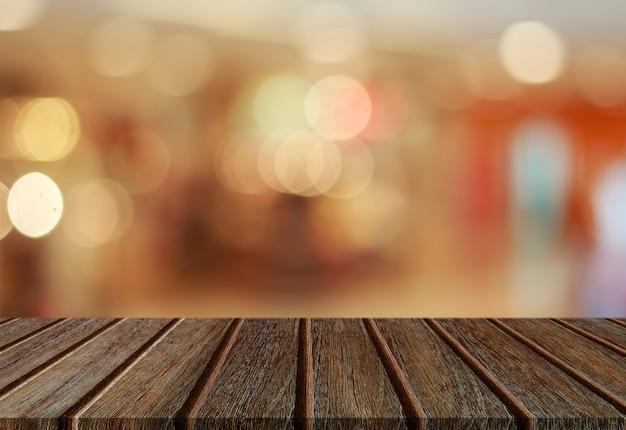 Plankentischplatte der leeren perspektive hölzerne mit abstraktem bokeh lichthintergrund für montage ihres produktes.