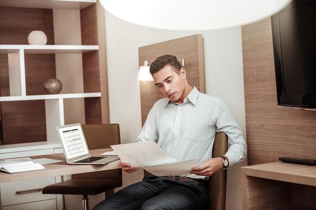 Planmäßig arbeiten. vielbeschäftigter, dunkelhaariger, erfolgreicher geschäftsmann, der planmäßig für seine mitarbeiter arbeitet