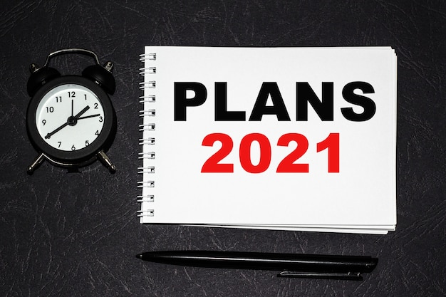 Plans 2021 inschrift auf einem weißen fragment. notizbücher, uhr und ein stift auf dem tisch zur information