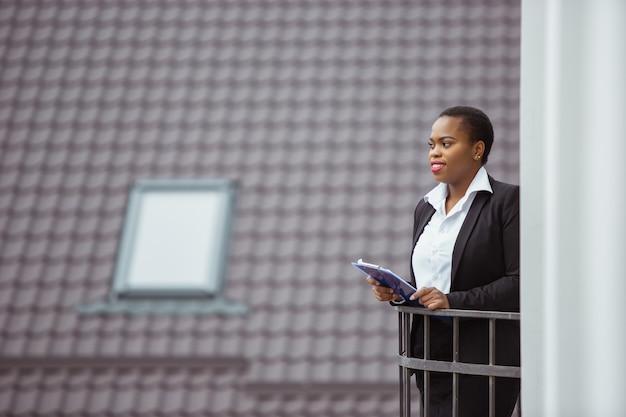Planung. afroamerikanische geschäftsfrau in bürokleidung lächelnd, sieht selbstbewusst und glücklich aus, beschäftigt. konzept für finanzen, wirtschaft, gleichstellung und menschenrechte. schönes junges weibliches modell, erfolgreich.