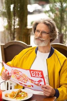 Planung der exkursion. nachdenklicher bärtiger mann mit einem stadtplan in der hand, der zu mittag isst und auf die straße schaut, bevor er geht.
