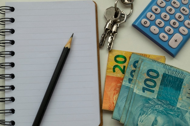 Planung der immobilienvermietung. brasilianisches geld, taschenrechner, notizblock, bleistift und schlüssel.