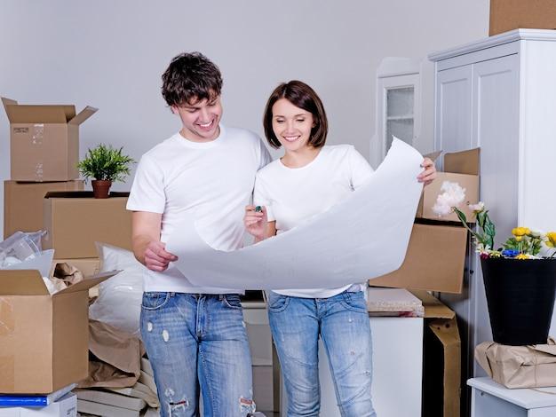 Planung der zukünftigen wohnung durch ein junges fröhliches paar