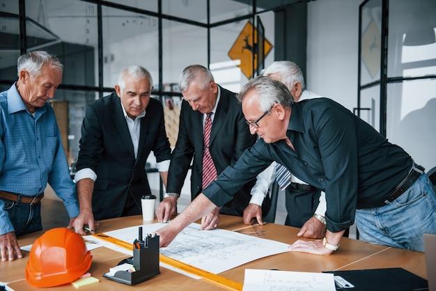 Planung des baus durch vermessen auf papier. ein gealtertes team älterer geschäftsmannarchitekten trifft sich im büro.