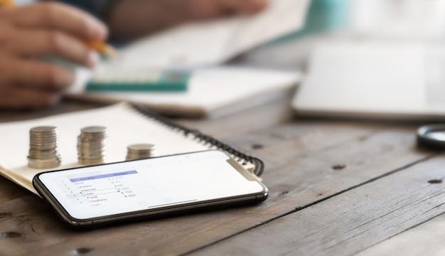 Planung des monatlichen home-budget-konzepts. smartphone mit einer liste der ausgaben für den monat auf holztisch