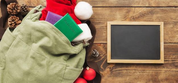 Planung für die reise. rucksack mit tafel, pass, weihnachtsmann-hut und weihnachtsfestdekorationen auf holztisch.