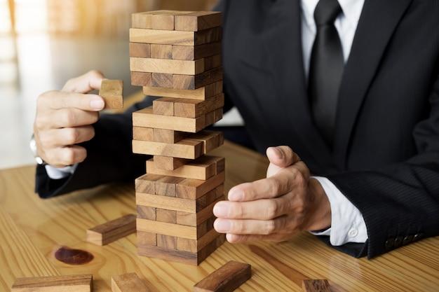 Planung, risiko und reichtum strategie in business-konzept, geschäftsmann und versicherung glücksspiel platzierung holzblock auf einem turm