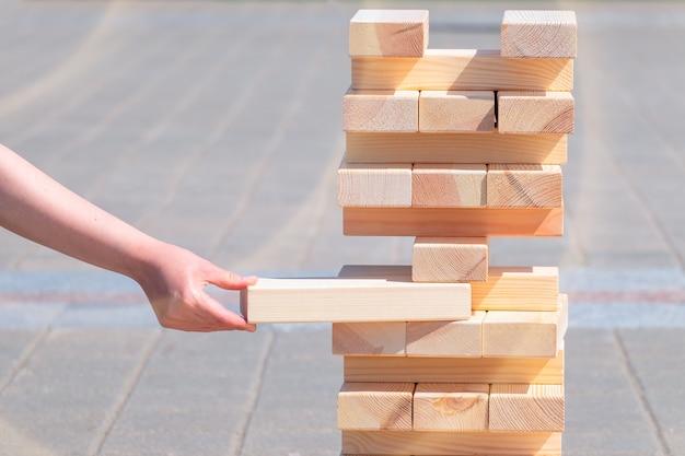 Planung, risiko und strategie im geschäft. geschäftsmann, der holzblock auf einen turm setzt