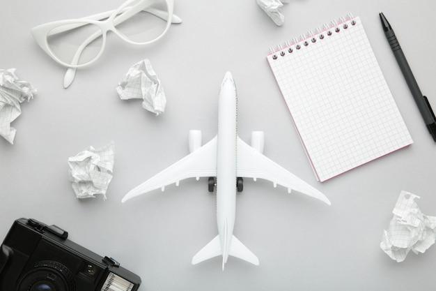 Planung von sommerferien, tourismus und reise vintage hintergrund. reisetagebuch mit zubehör auf grau. flach liegen.