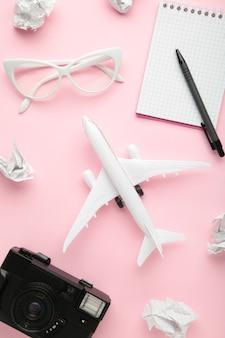 Planung von sommerferien, tourismus und reise vintage wand. reisetagebuch mit zubehör auf rosa. flach liegen.
