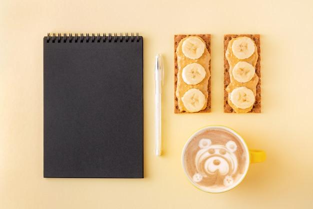 Planung während des frühstücks mit cappuccino und knusprigen getreidecrackern mit nussbutter auf gelb