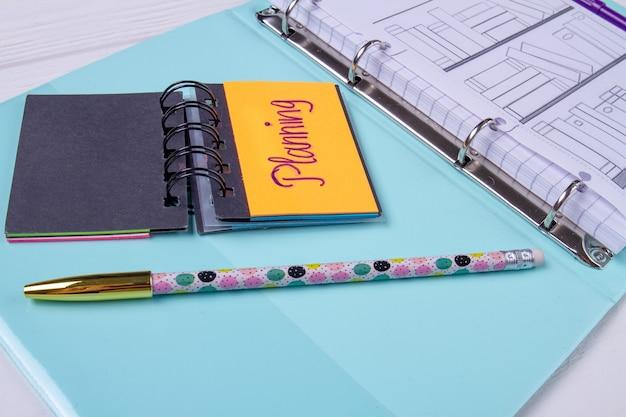 Planungskalender und stift auf blauem blatt.