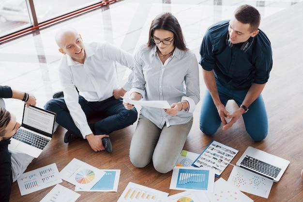 Planungsstrategie zusammen. geschäftsteam, das papiere auf boden mit dem manager zeigt auf eine idee betrachtet. kooperation unternehmensleistung. planungsentwurf zeichnen. teamwork-konzept
