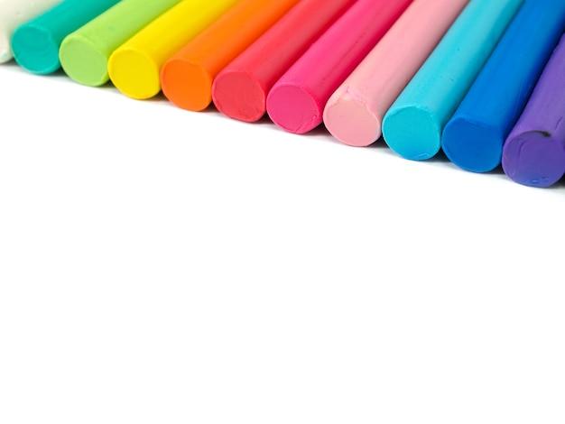 Plasticine des bunten kindes auf weißem hintergrund, bunter teig, der lehm modelliert