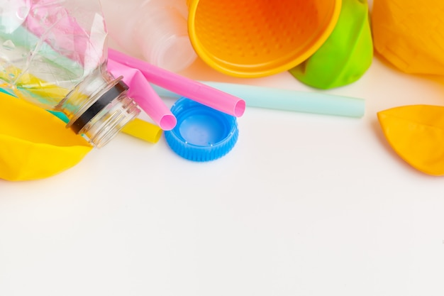 Plastikabfallgefahrenökologie mit abfall und bunten einwegstrohen, tischbesteckschalen, flaschen auf weiß