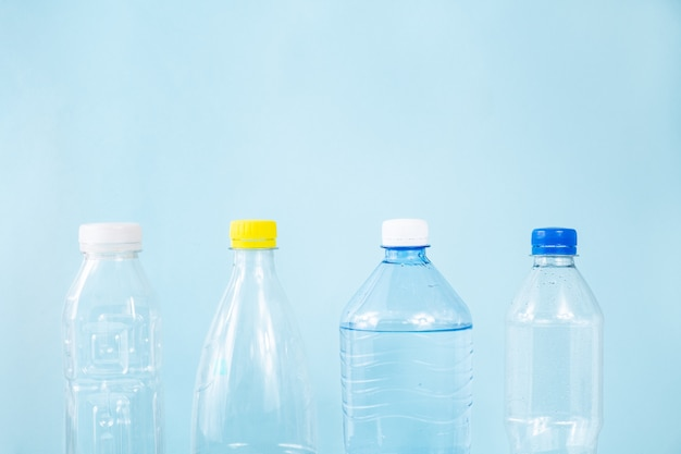 Plastikabfallkonzept: weggeworfene verschiedene wasserflaschen im blauen hintergrund