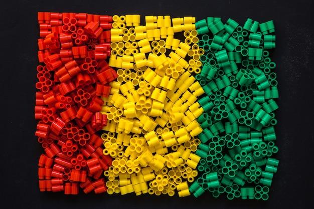 Plastikbausteine in rot, gelb und grün auf schwarzem hintergrund. details zu spielzeug. ansicht von oben.