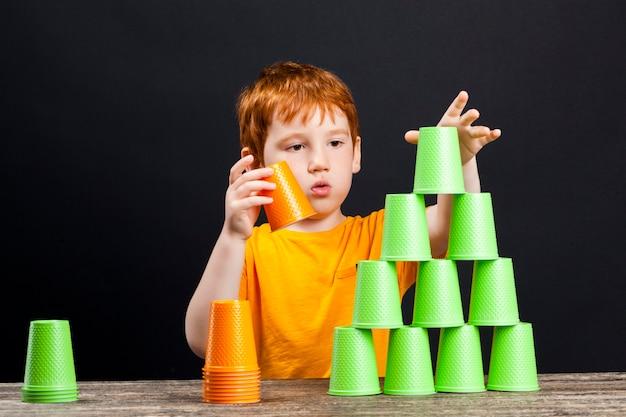 Plastikbecher, die das kind während des spiels zusammengestellt hat