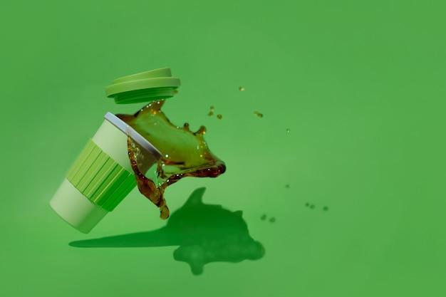 Plastikbecher kaffee, der auf einen grünen hintergrund fällt und verschüttet.