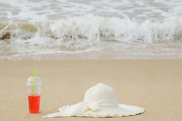 Plastikbecher mit einem roten erfrischungsgetränk und dem breitkrempigen hut am strand