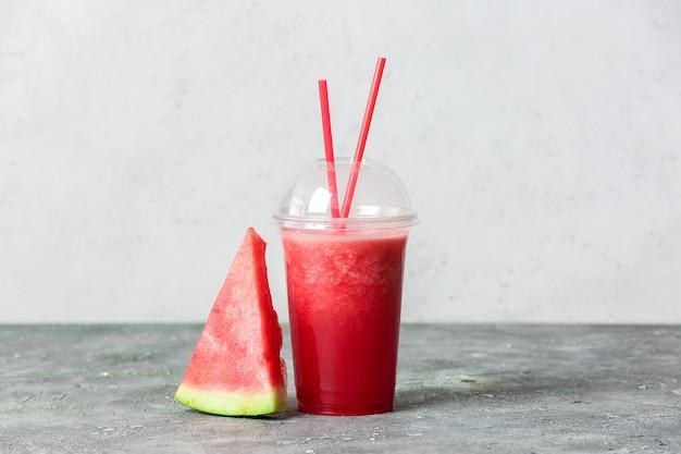 Plastikbecher mit frischem wassermelonensaft auf grau