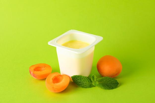 Plastikbecher mit joghurt und früchten auf farbigem hintergrund,