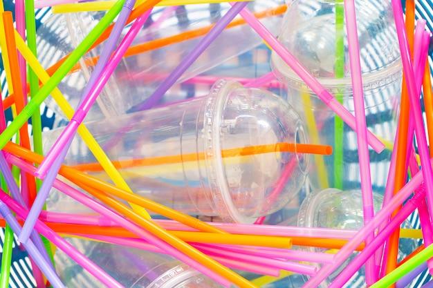 Plastikbecher mit strohhalmen im papierkorb.