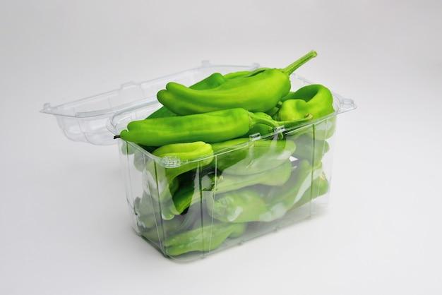 Plastikbehälter mit grünem paprikaschotenpfeffer lokalisiert auf einem weißen hintergrundpfefferausschnitt