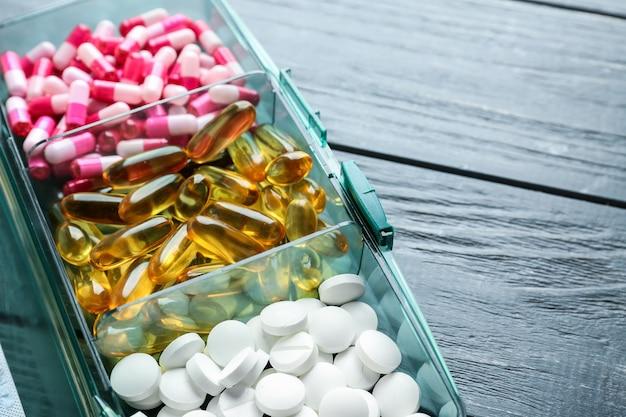 Plastikbehälter mit verschiedenen pillen auf holztisch