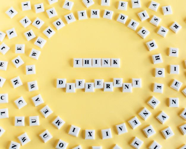 Plastikblockwürfel mit wort denken verschiedenes und herum zerstreute einzelne buchstaben auf gelb