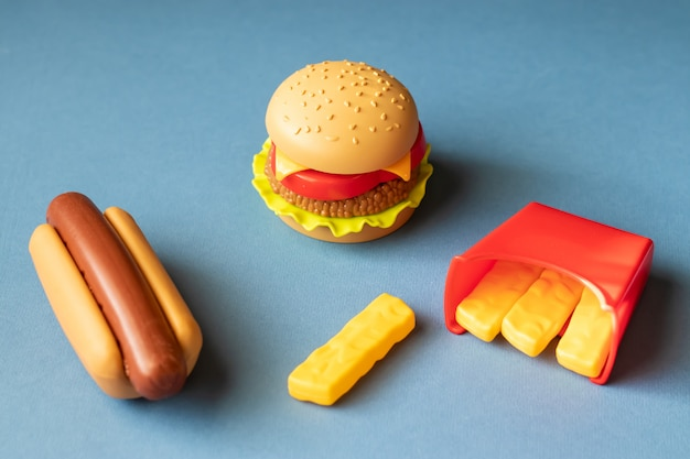 Plastikburger, salat, tomate, kartoffeln mit einem hotdog auf einem blauen hintergrund bratend