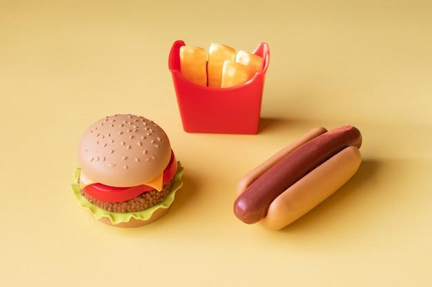 Plastikburger, salat, tomate, kartoffeln mit einem hotdog auf einem gelben hintergrund bratend