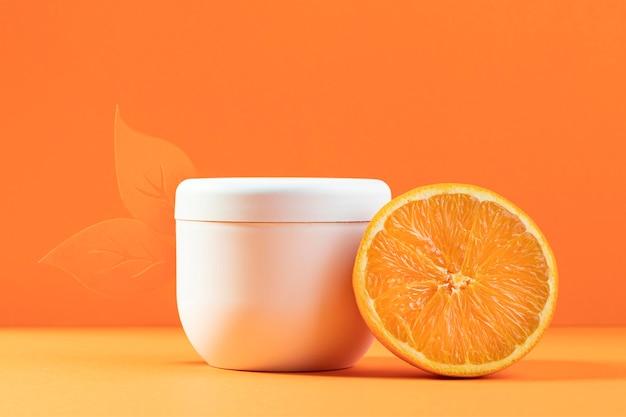 Plastikcremebehälter mit orangefarbener hälfte
